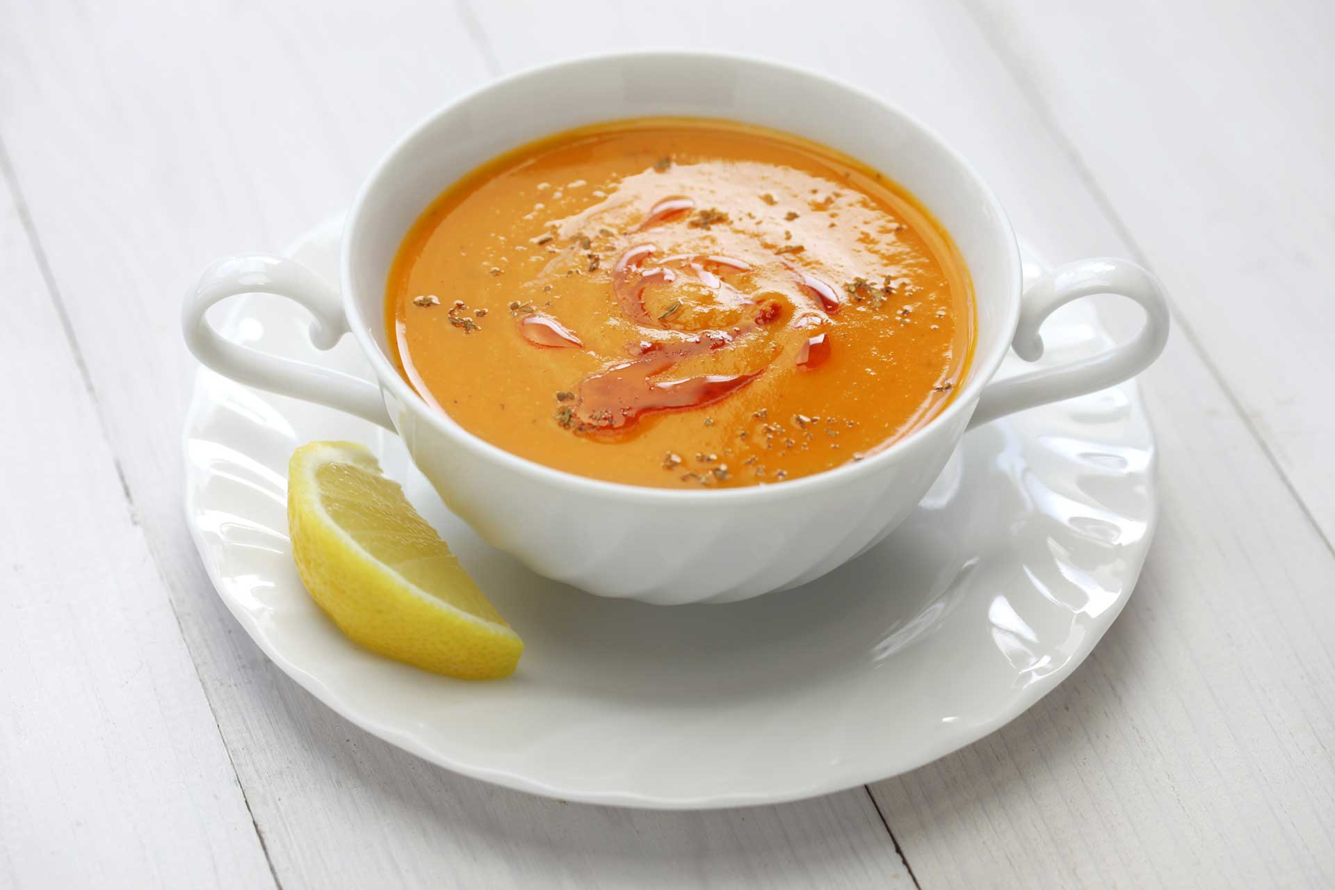 quick and low fat easy to cook Turkish red lentil soup, in a white bowl with slice of lemon on the side