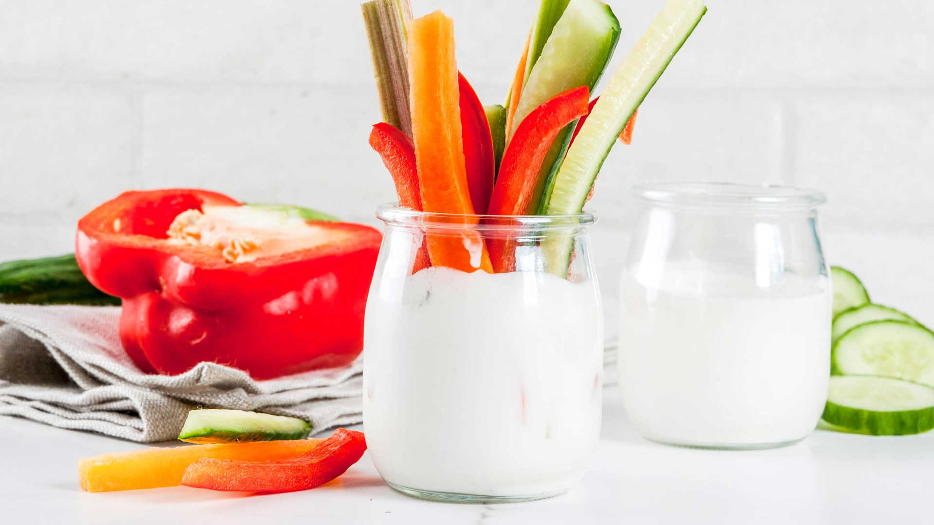 Summer healthy snack appetizer, assorted colorful fresh vegetable sticks (celery, rhubarb, pepper, cucumber and carrot) with yoghurt sauce dip, white marble background copy space
