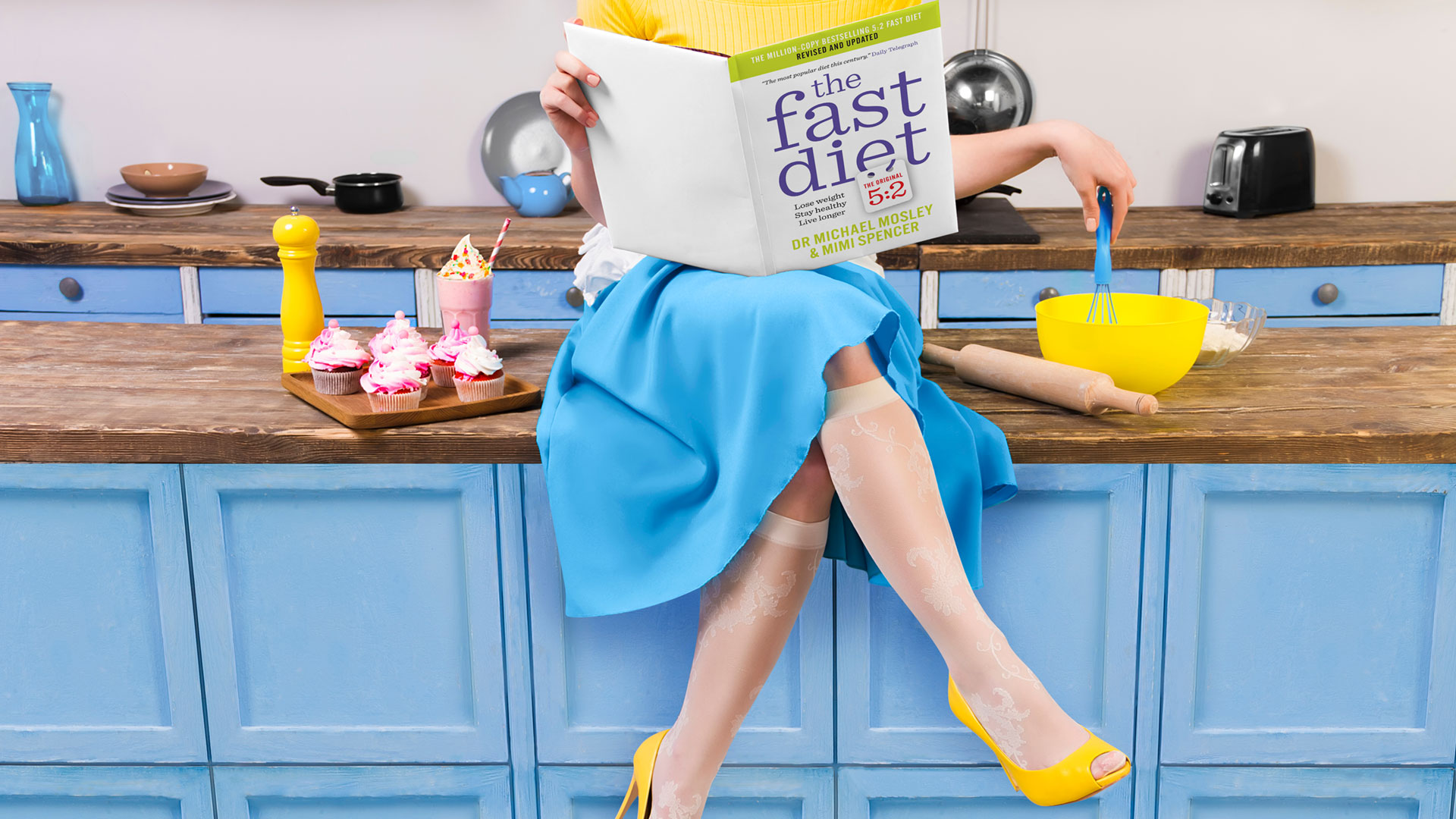 Retro woman wearing yellow top, skirt and white apron sitting on kitchen counter and reading the fast diet book. Sweet food cupcakes and milkshake home cooked on the table