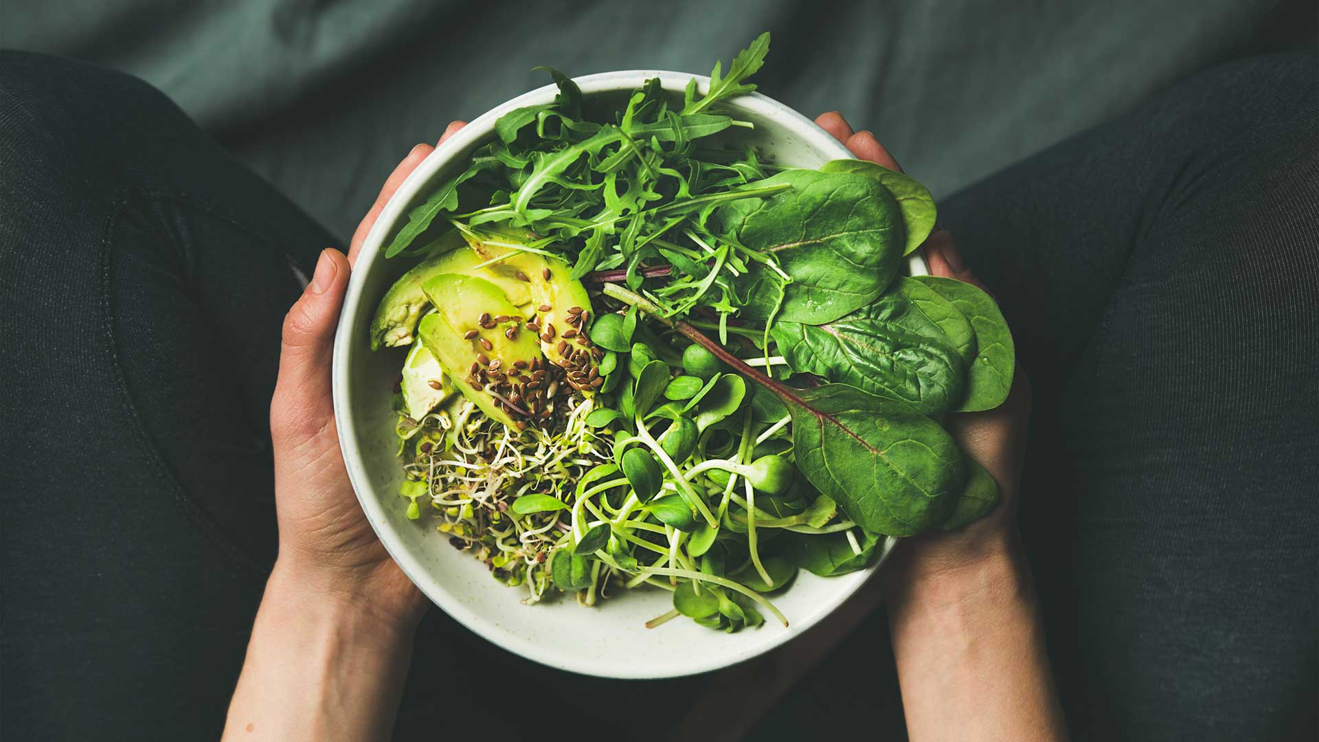 A white bowl of healthy greens and leaves held in two hands over a dark blue background