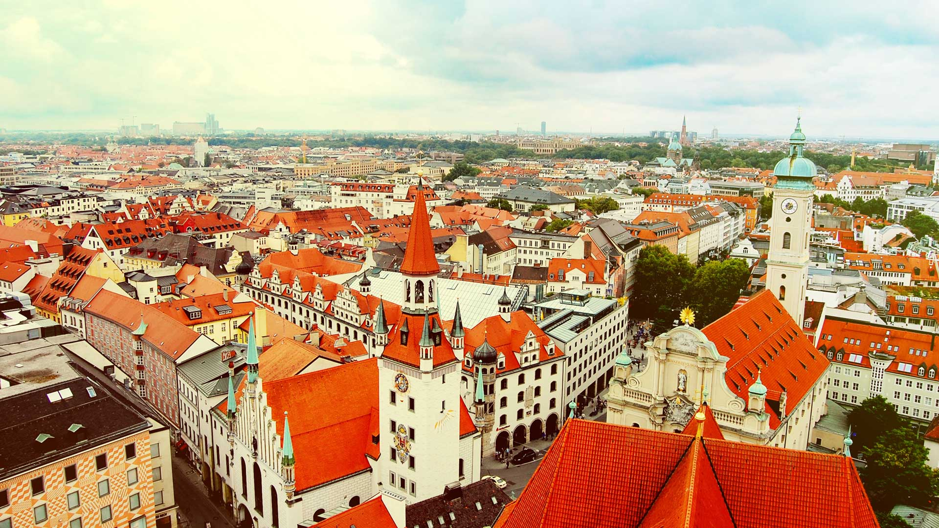 Skyline of Munich from high vantage point, with white buildings with red roofs and a cloudy blue sky
