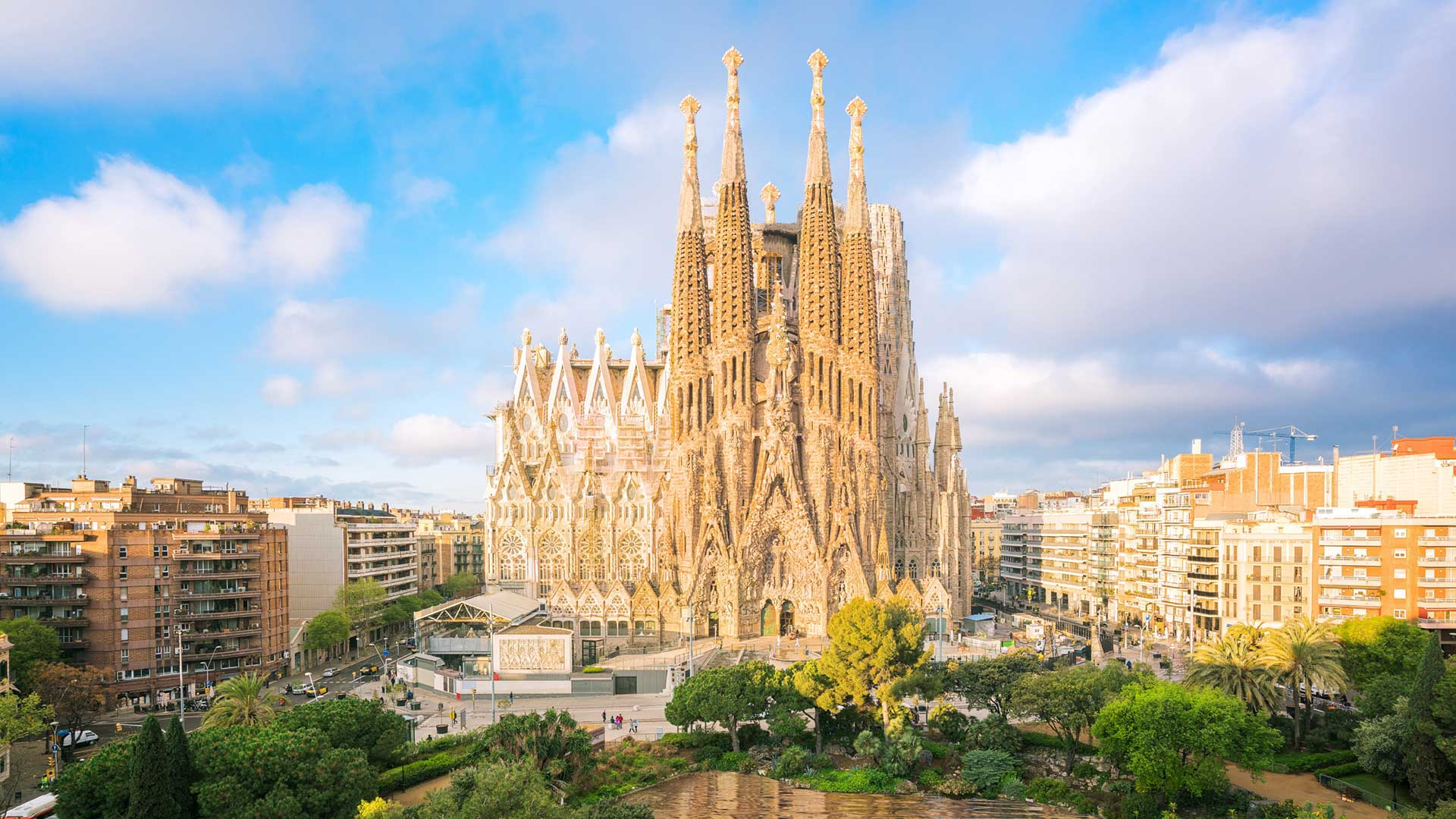 The Sagrada Familia, a yellow church rising above the city with a blue sky in the background