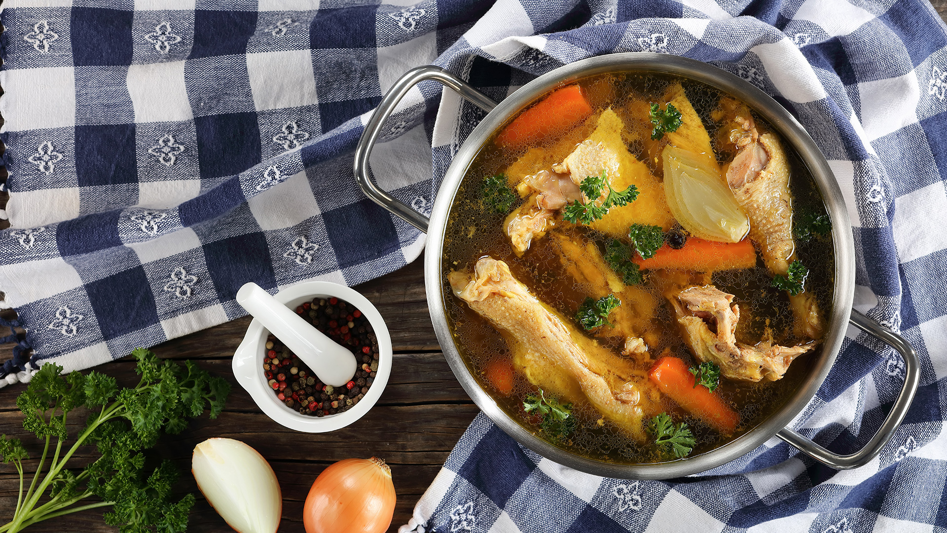 Clear Chicken broth with pieces of hen and rooster meat on bone in a metal cooking pot on wooden table with kitchen towel and ingredients on wooden table, view from above