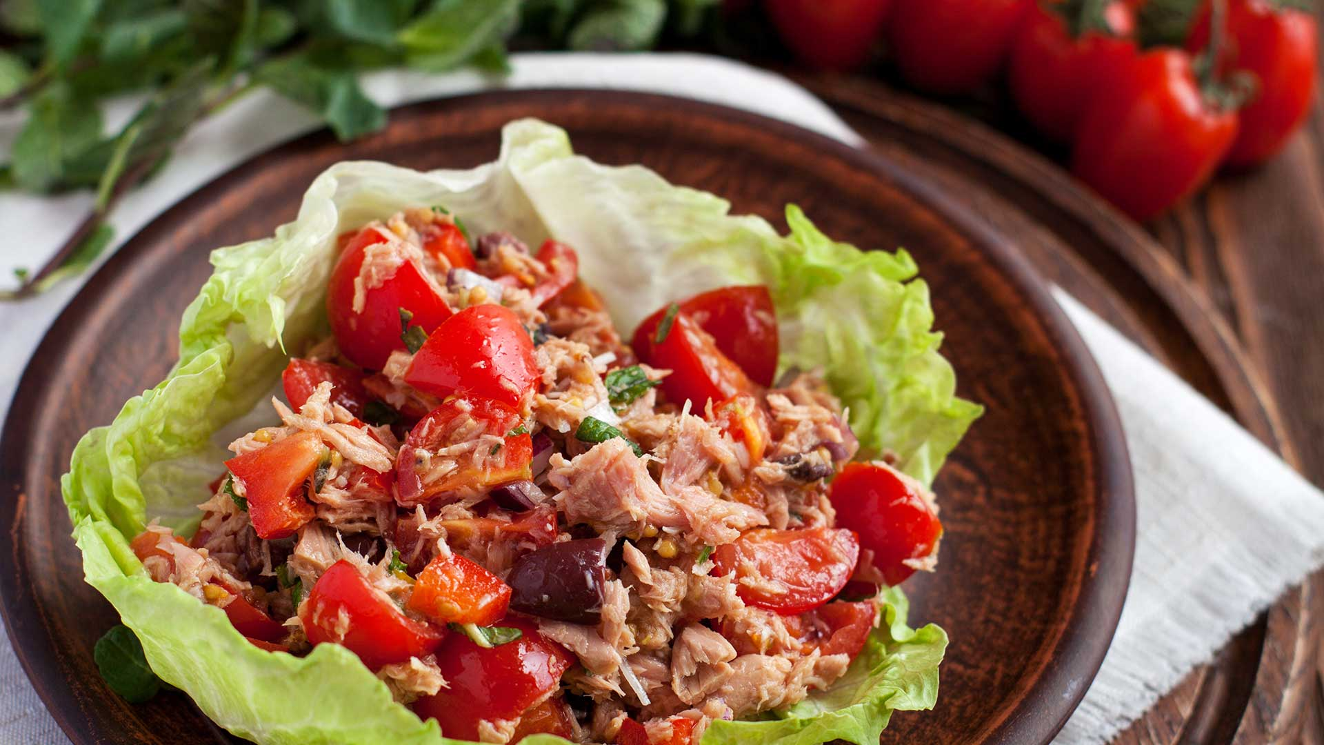 Healthy appetisers lettuce wraps with canned tuna, bell pepper, herbs on clay plate