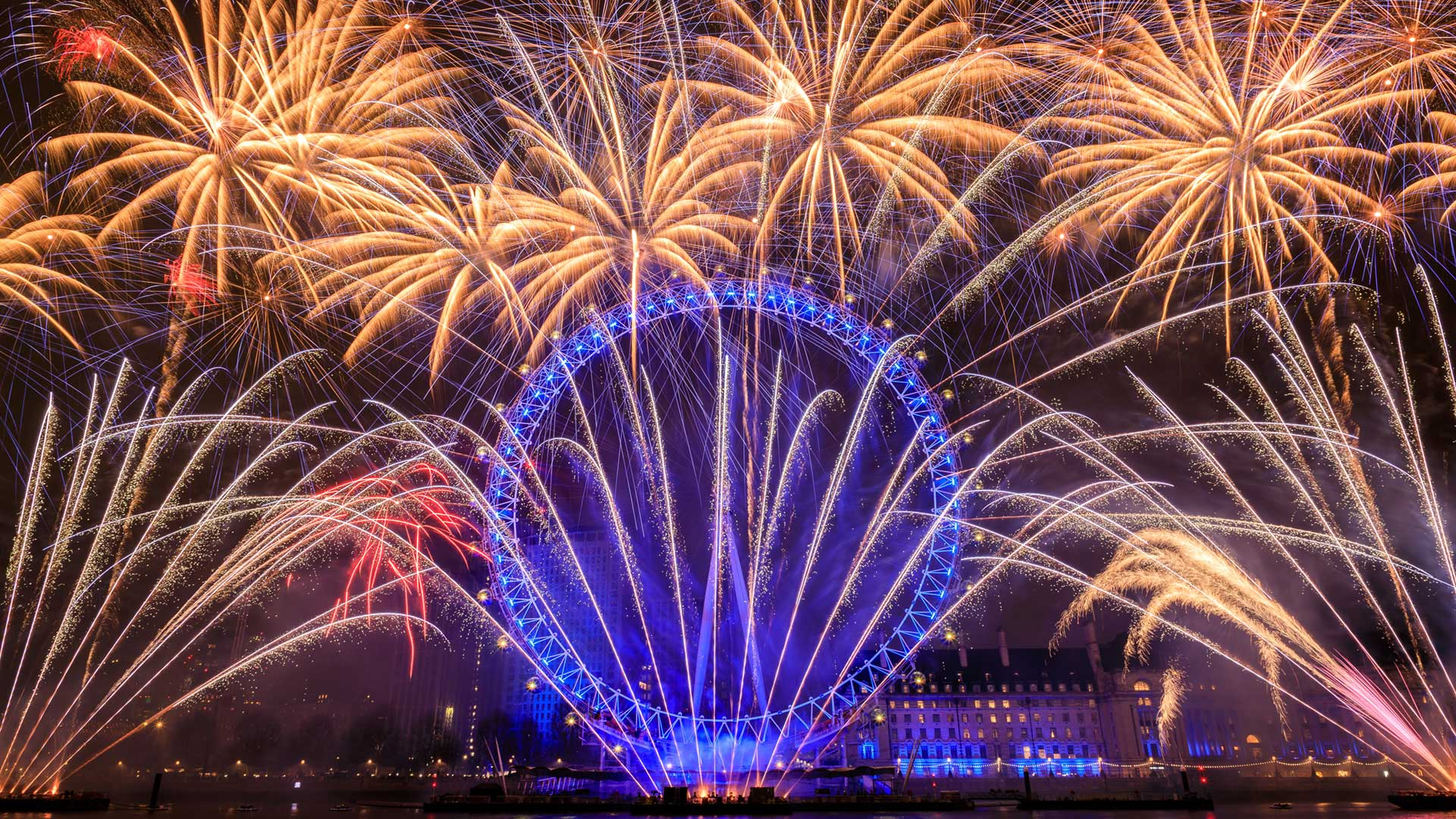 London Eye ferris wheel lit by blue lights with a golden fireworks display surrounding it against the night sky