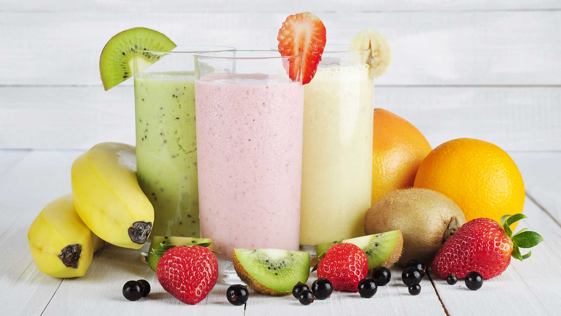 kiwi, strawberry and banana smoothies in a glass with fruits around them on a white wooden table