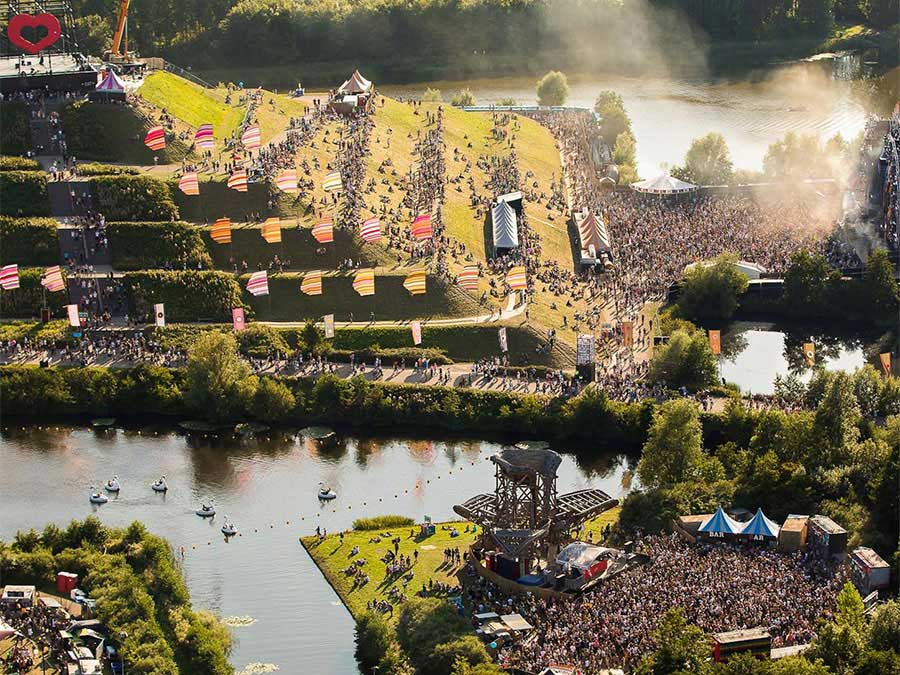 Crowds fill the two main stages and climb the vast green step pyramid in the middle of the lake at Mysteryland Festival