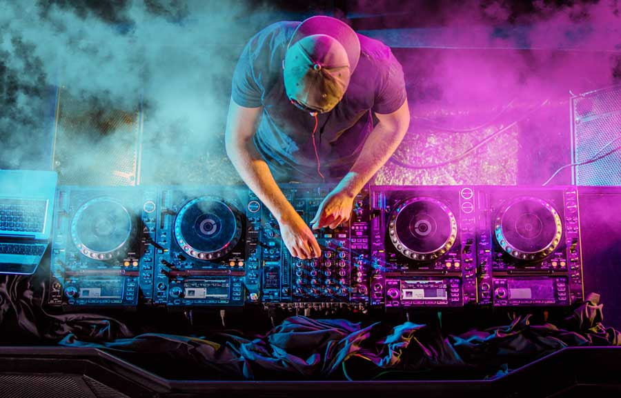 Top down view of a DJ at the turntable, lit by blue and purple lights and surrounded by smoke
