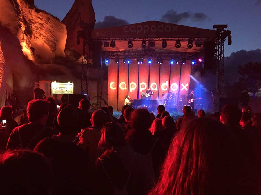 A stage at Cappadox music festival with festivalgoers in the foreground and cliffs in the background