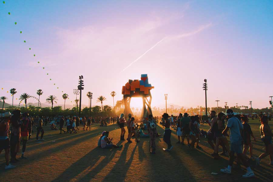 sun setting behind art installation at coachella, california