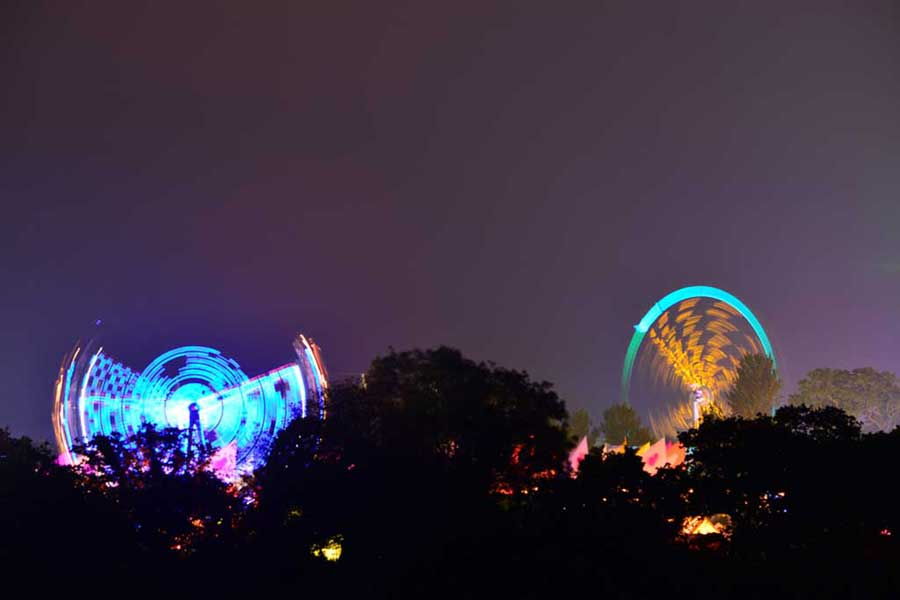 Blurred ferris wheels lit up against a dark sky background, with trees silhouetted in the foreground
