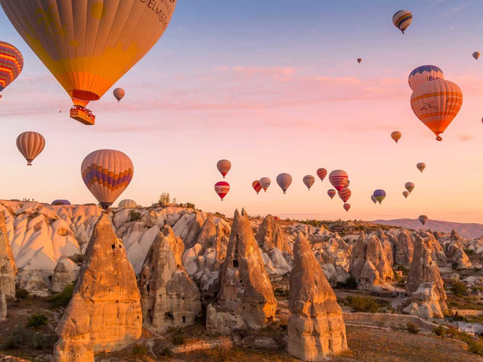 Hot air balloons filled with tourists during a pink sunrise floating along valleys of Göreme National Park