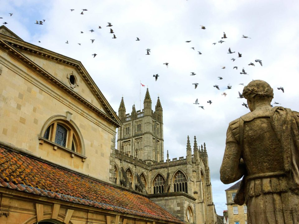 Stone statue of the roman in Antique Roman Baths complex, flying birds in sky and Abbey Cathedral at background.