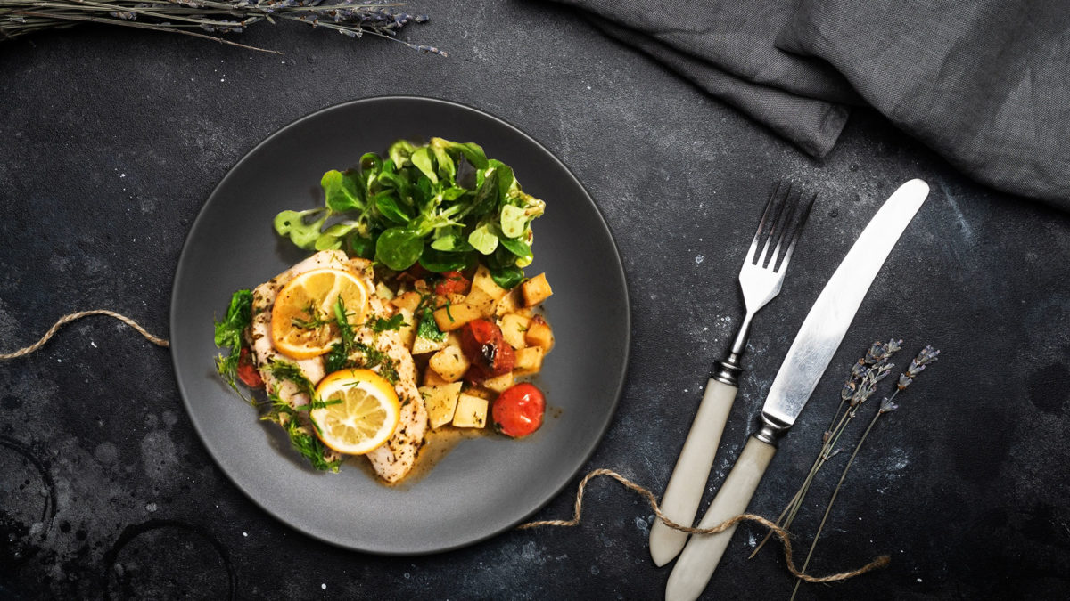 Baked Lemon & Herb Fish With Cherry Tomatoes on black plate with black dinner table and cutlery set