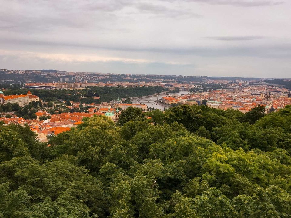 Panoramic view of the city of Prague with green forest and red roofs